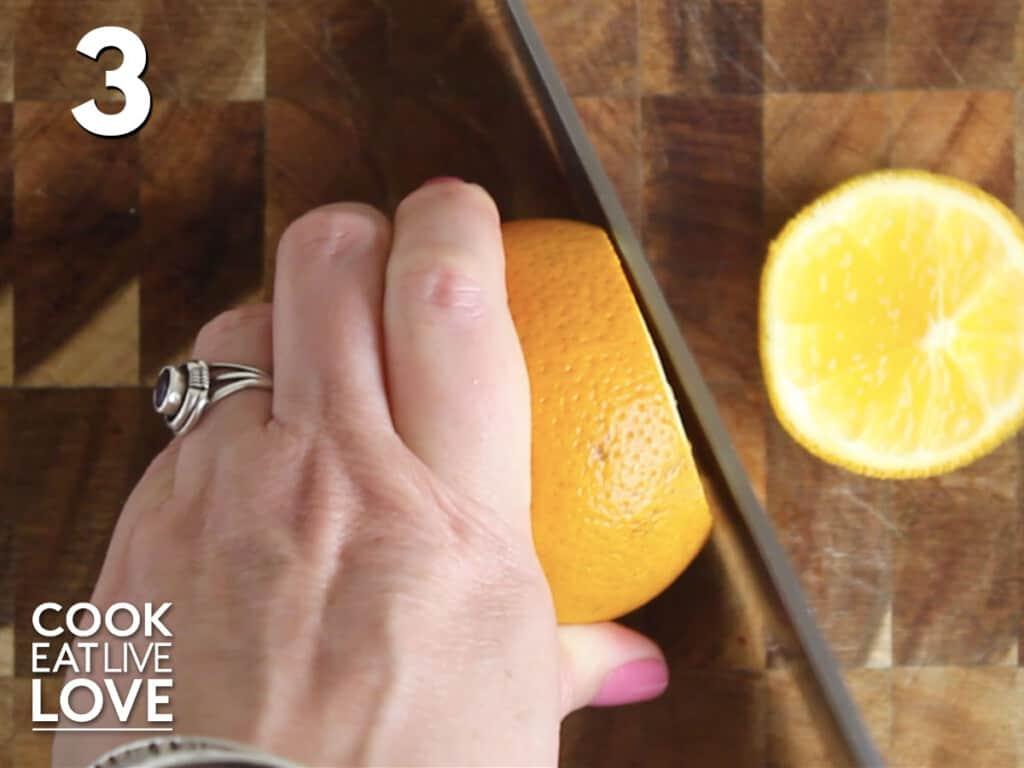 Slicing an orange on cutting board