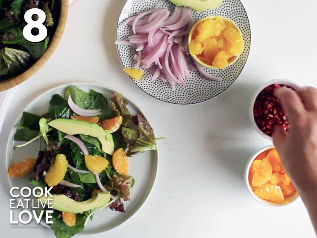 Adding ingredients to plate of salad on table