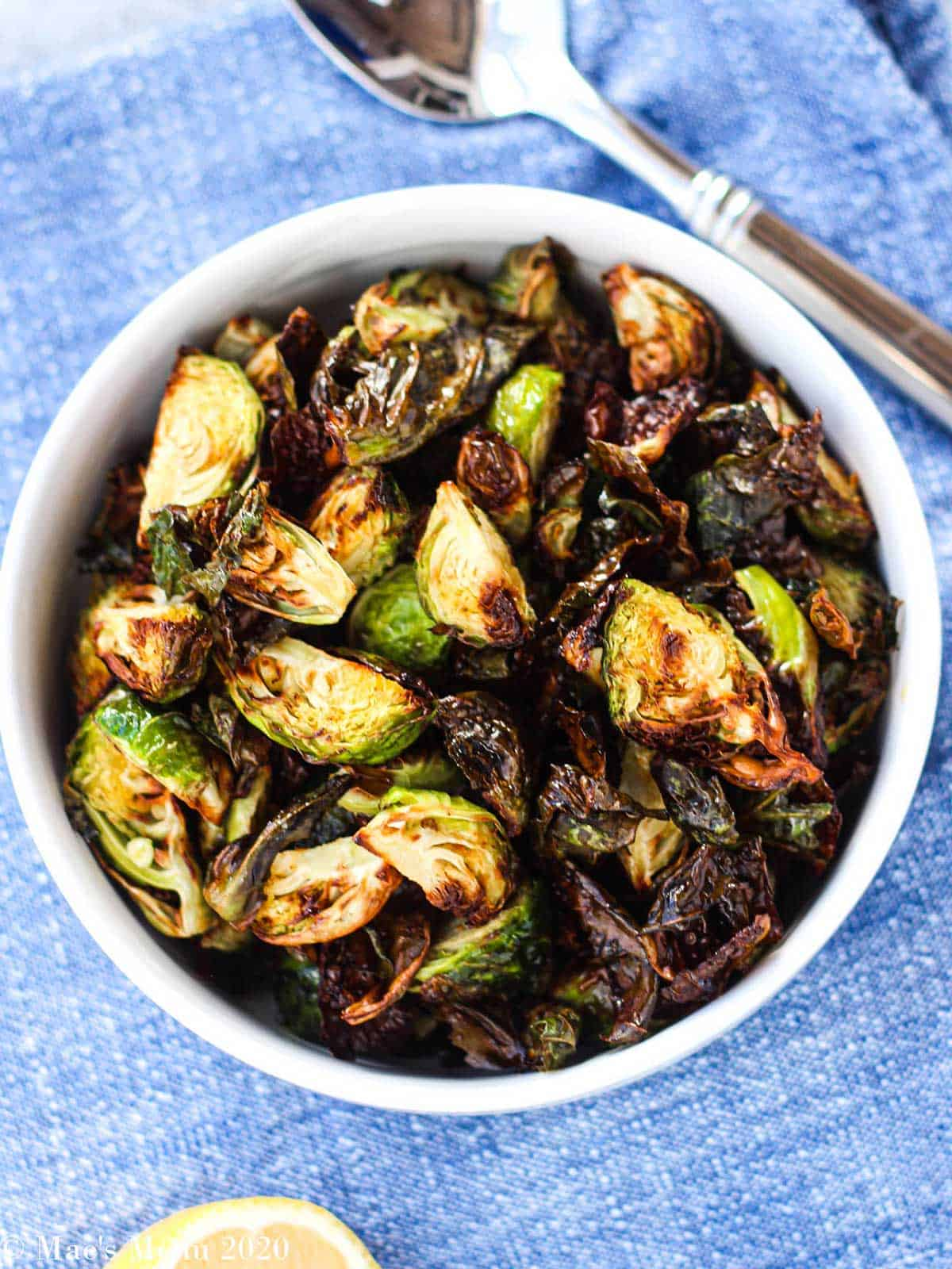 Cooked brussel sprouts in a white bowl on blue surface with spoon and lemon in frame.