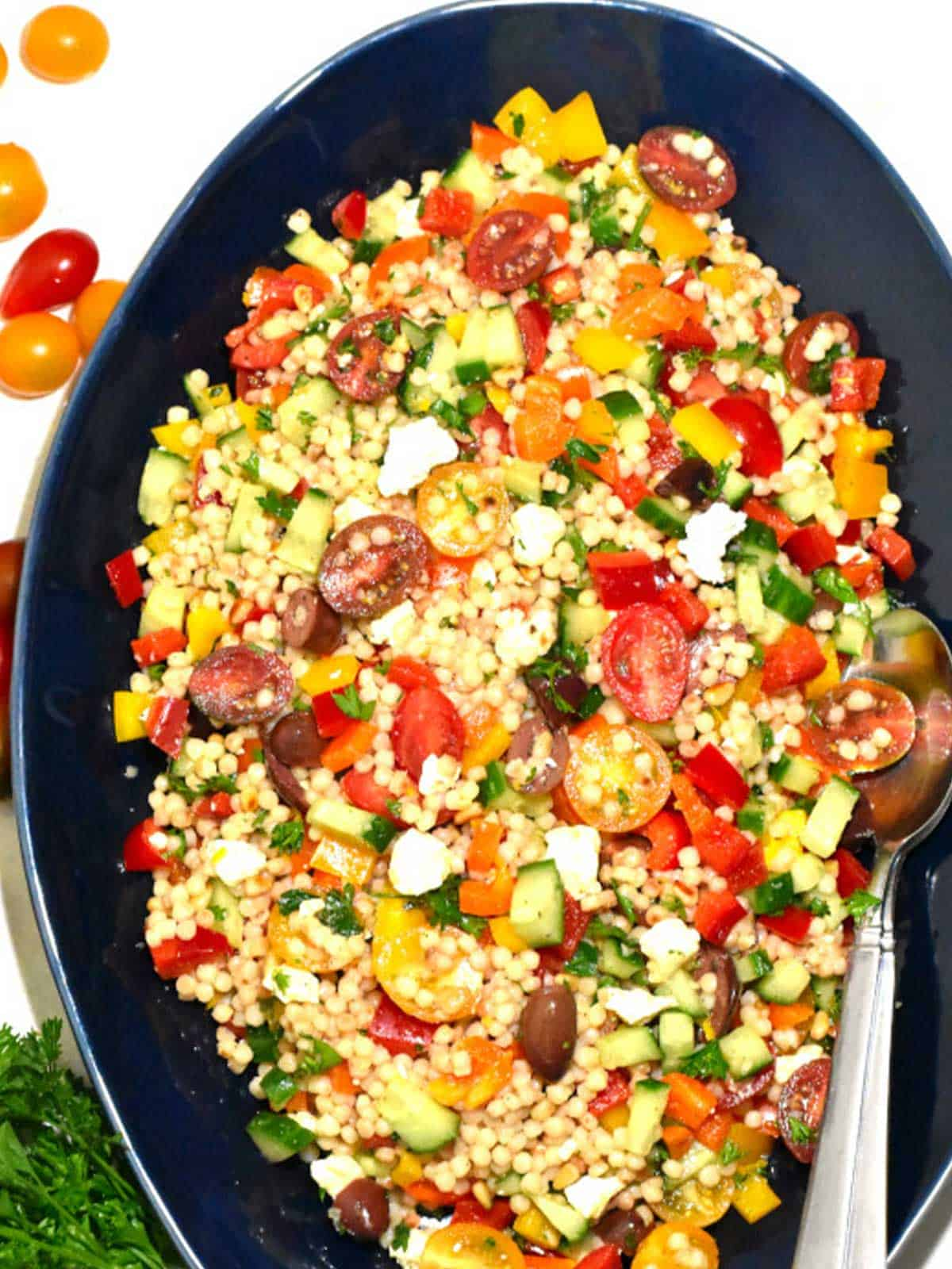 Overhead view of colorful couscous salad in an oval blue bowl surrounded by grape tomatoes.