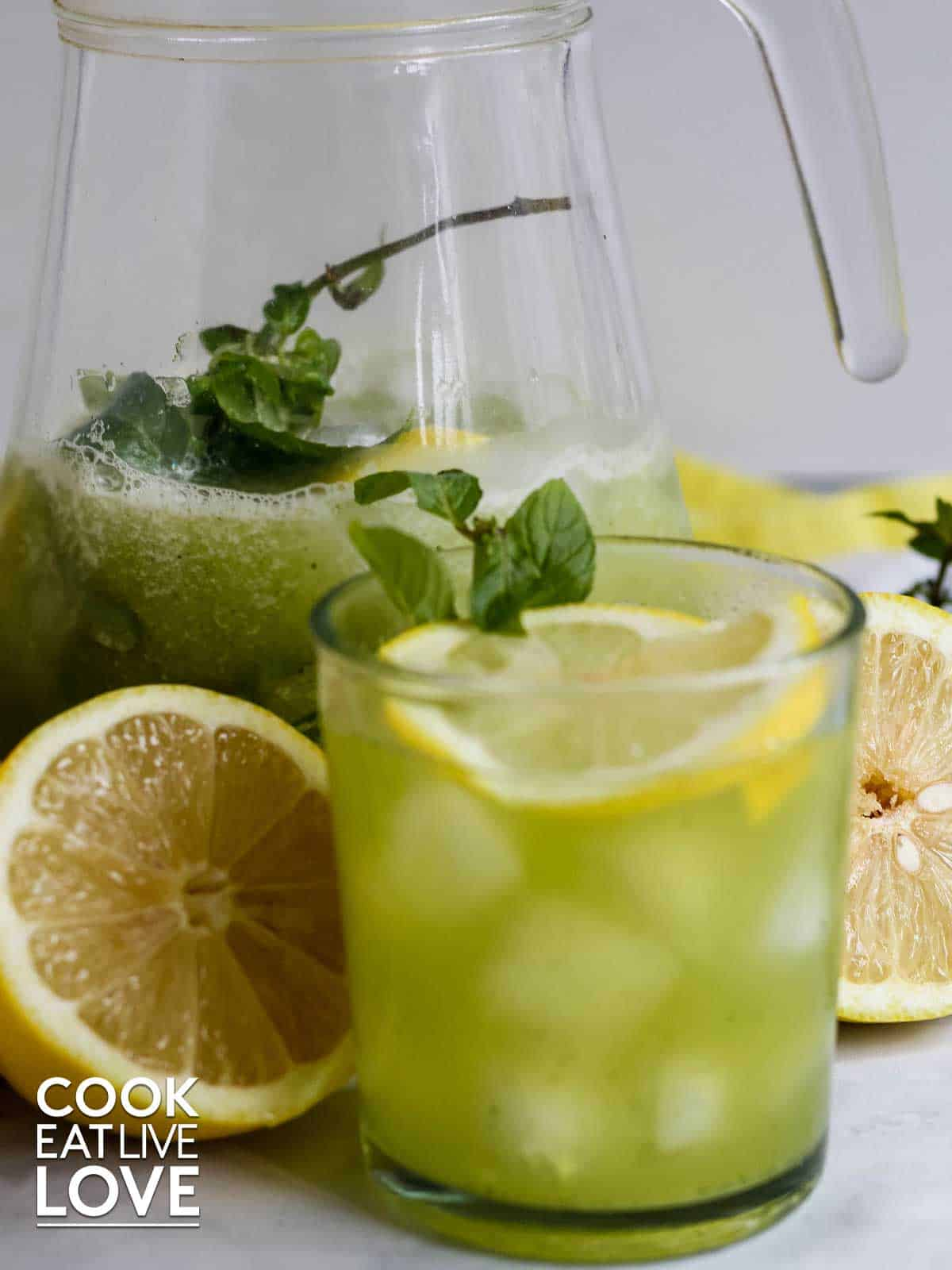 Glass filled with cucumber lemonade with lemon wheel floating on top. In background is pitcher with lemonade and lemon halves around both.