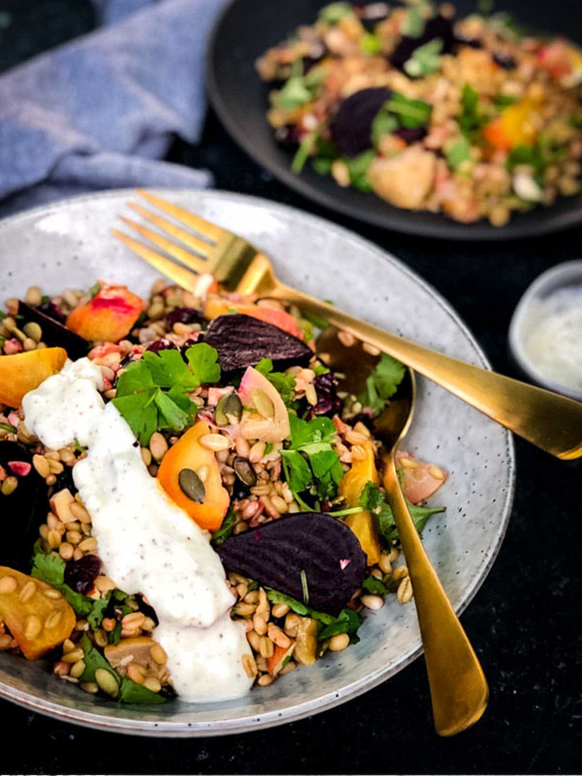 Bowl of salad with grains, beets and tomatoes and gold forks on bowl.  Behind is more salad and bowl of dressing.