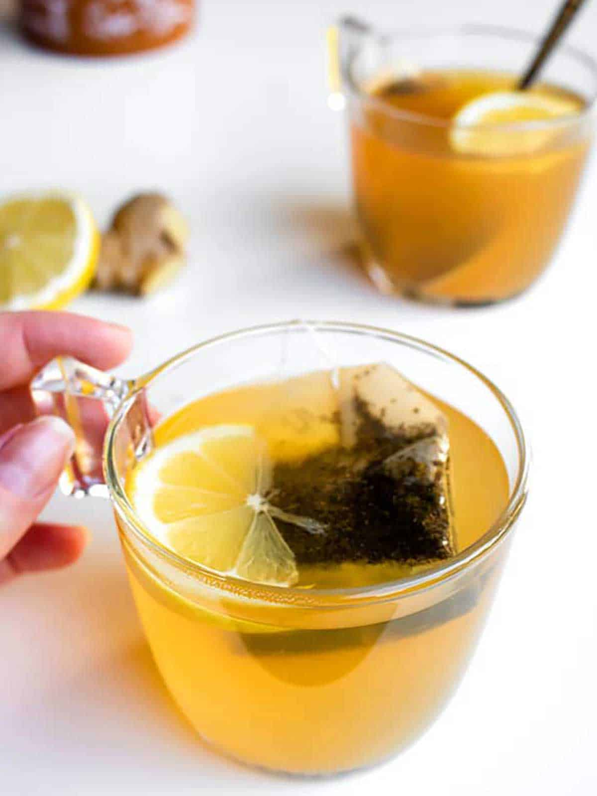 Glass mug with hand holding onto handle filled with tea and floating lemon slice.  In background another cup of tea, ginger and lemon.