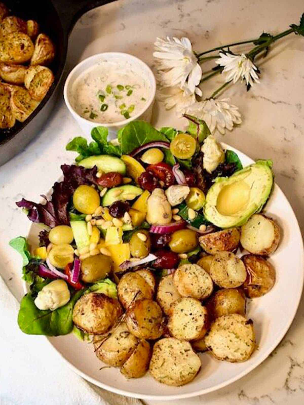 Plate filled with potatoes and veggie salad. Above is a sauce and pan of potatoes.