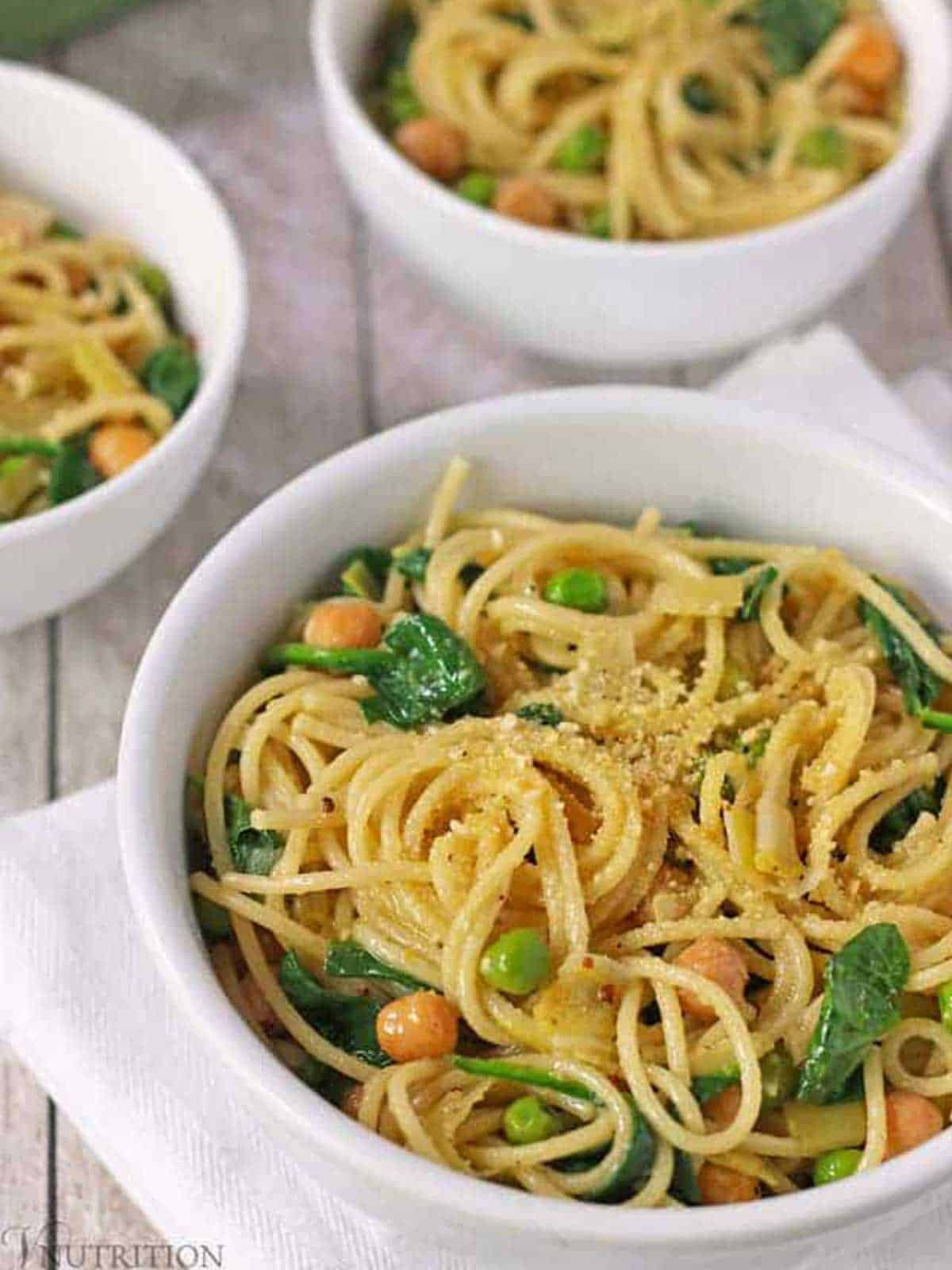 Bowls of pasta and veggies, peas, chickpeas and spinach on white surface.
