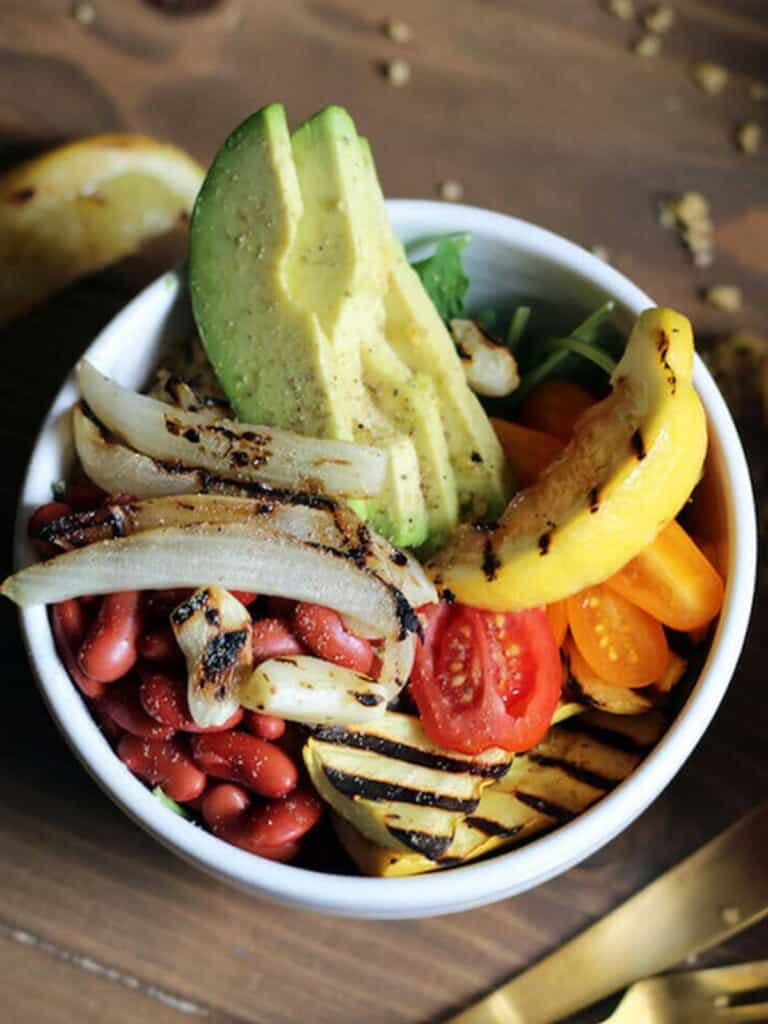 Overhead view of salad in white bowl with grilled vegetables, beans, avocado and grilled lemon wedge.