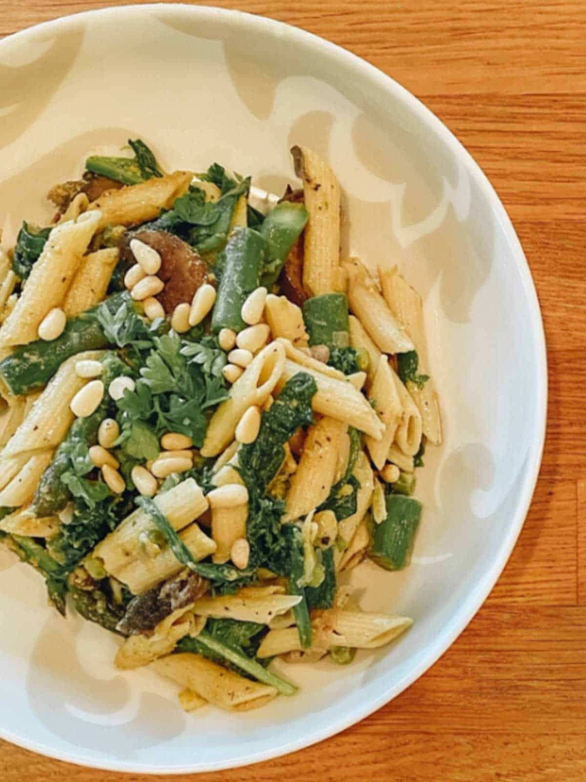 Overhead of pasta bowl with spinach, pinenuts and vegetables.