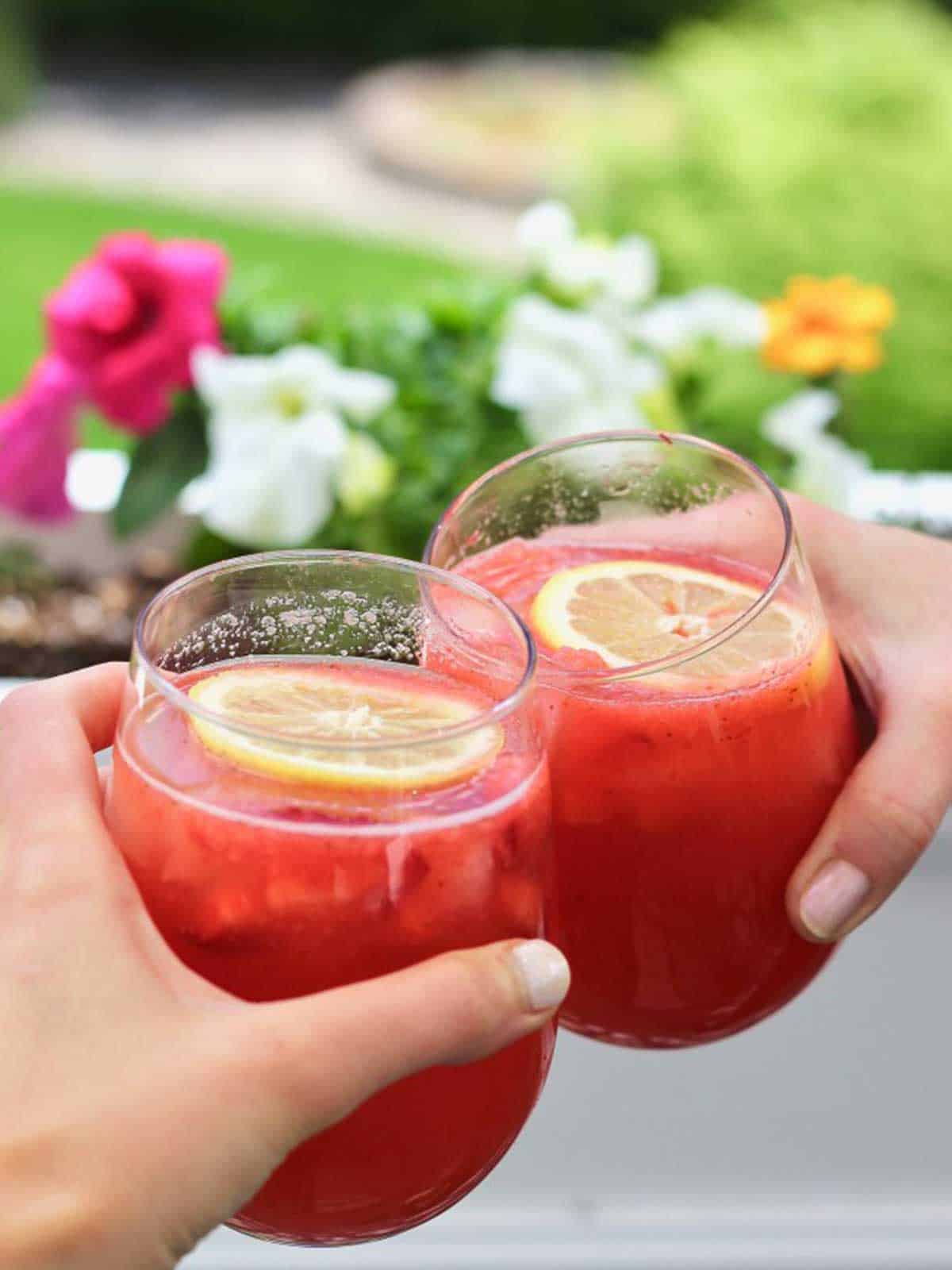 Two hands holding glass with red cocktail garnished with floating lemon slice clinking together to cheers.