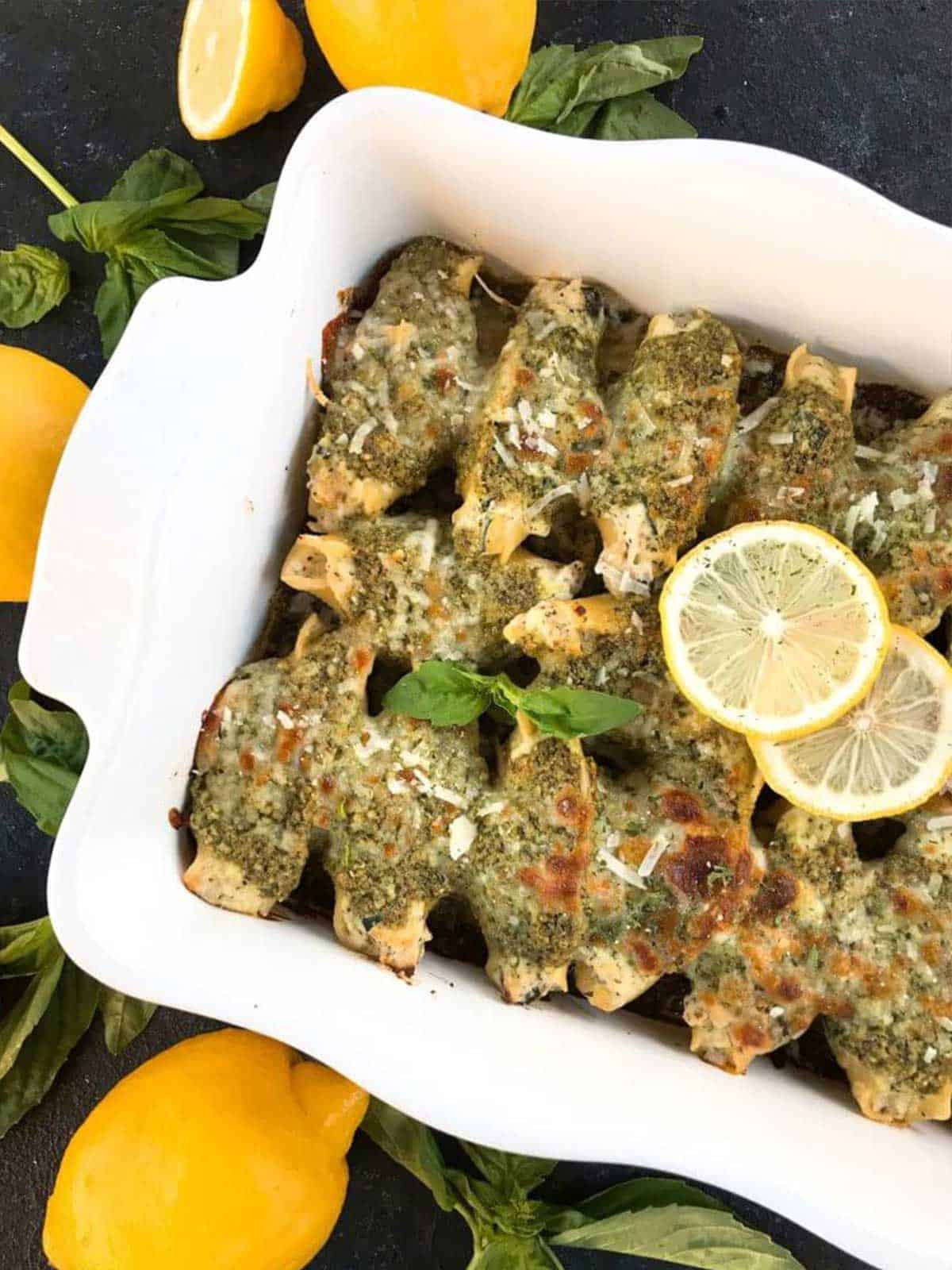 White casserole dish filled with stuffed shells topped with green sauce and garnished with lemon slices.
