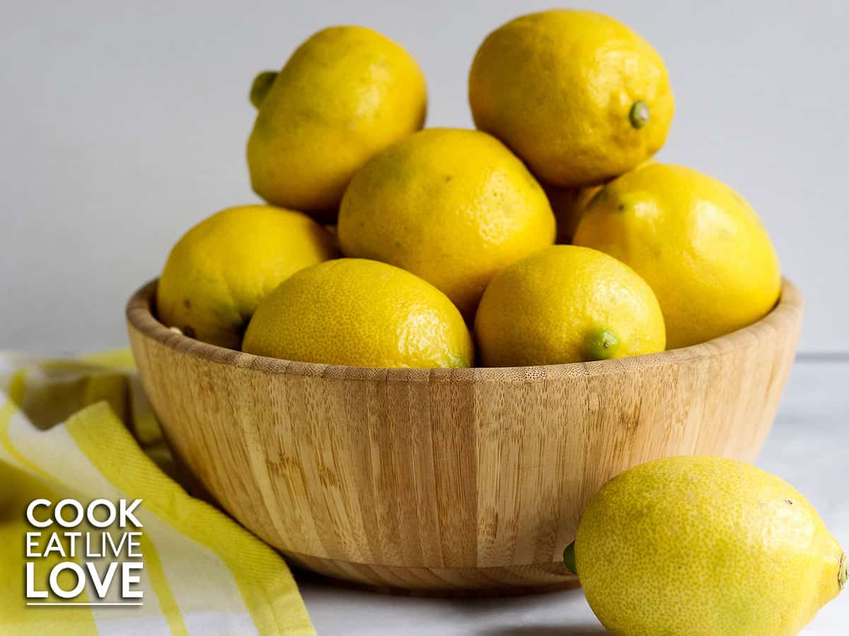 Wooden bowl filled with whole lemons.  One lemon in front on counter with yellow and white tea towel.