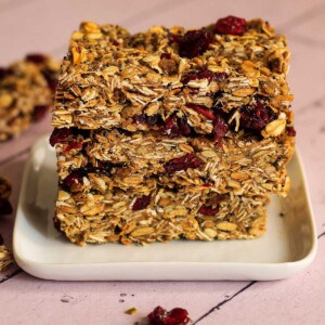 Vegan granola bars are piled up on small square plate.