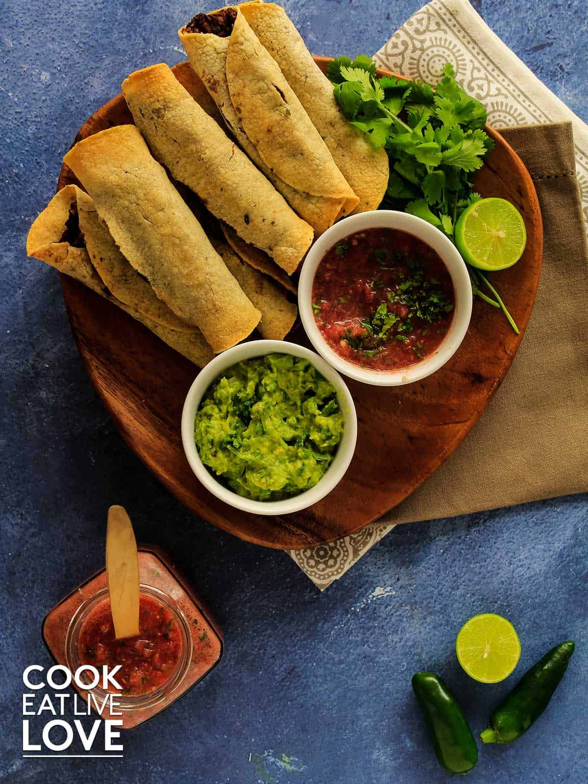 Taquitos on a plate with salsa and guacamole