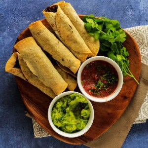Taquitos, guacamole, salsa on a wooden platter