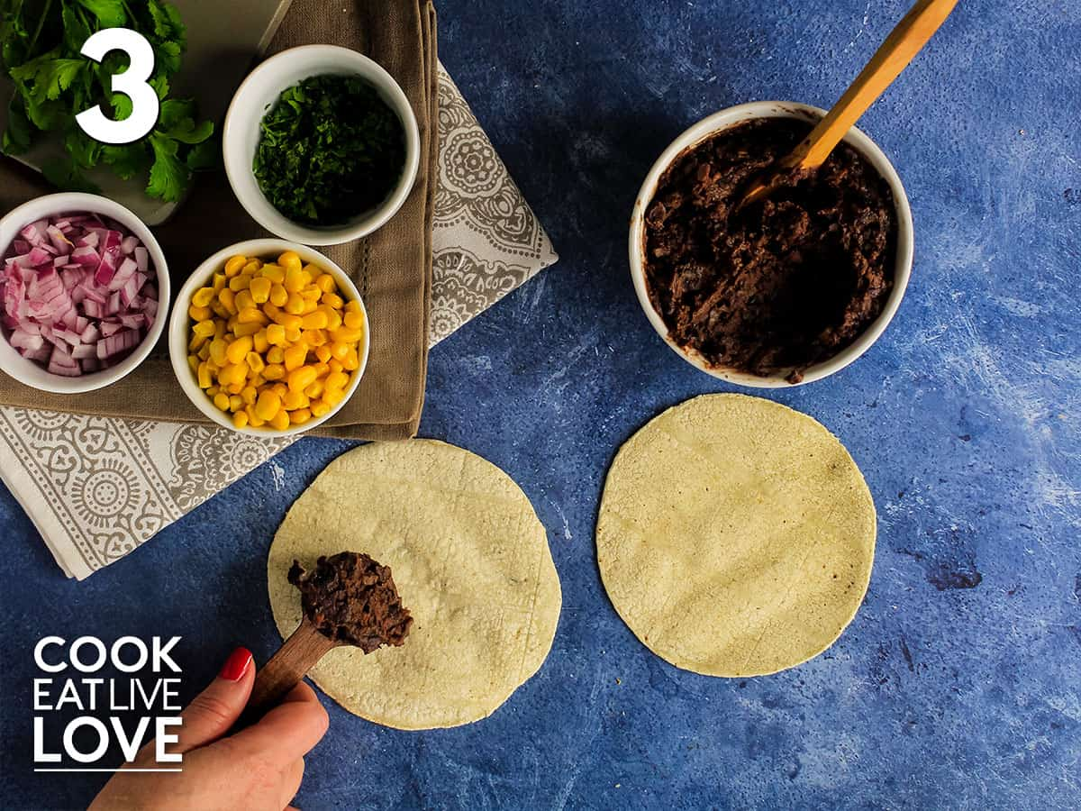 Black beans in tablespoon on corn tortilla