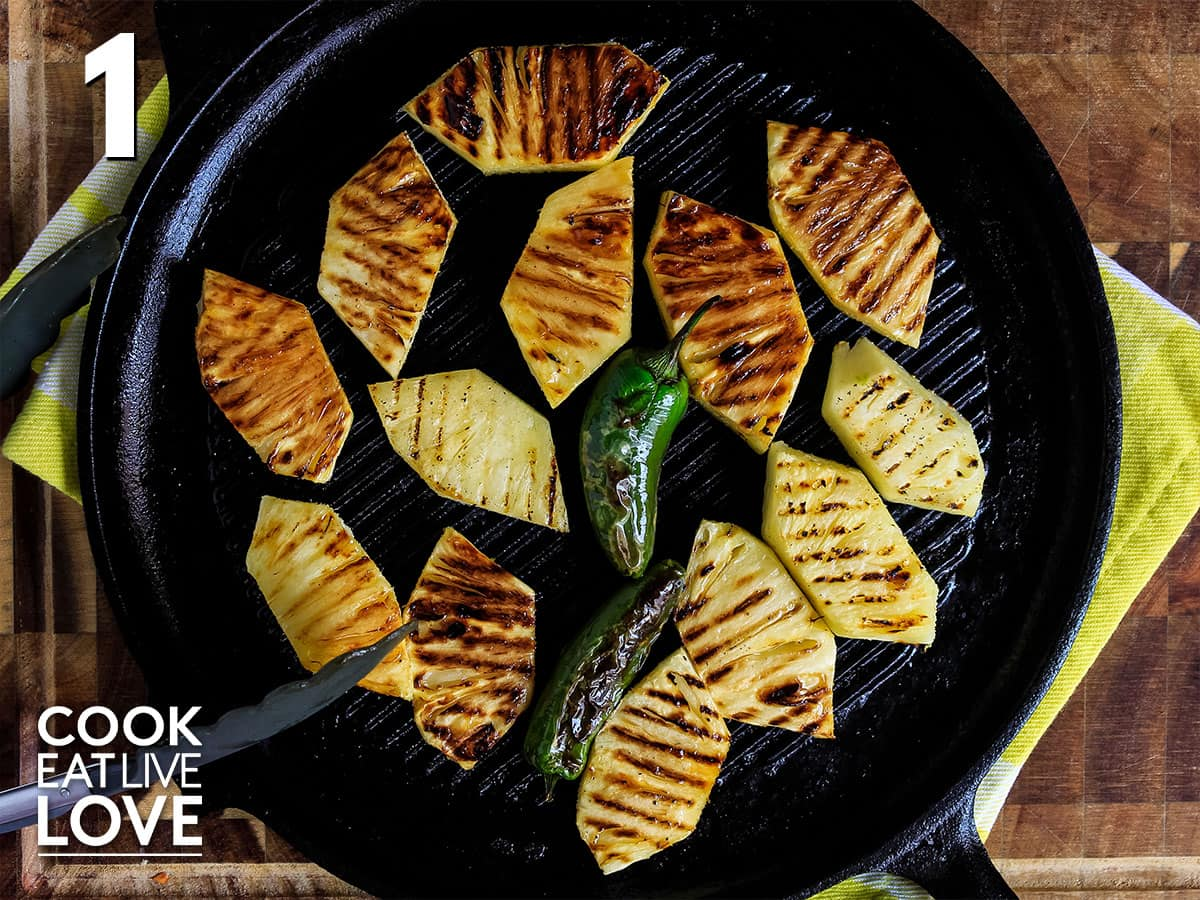 Slices of pineapple on a grill pan with jalapeno in the middle.