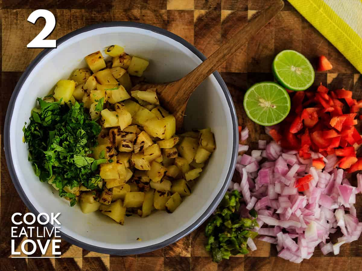 Pineapple and cilantro in white bowl with onions, red pepper and limes to juice on the side.