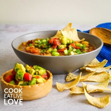 Gray bowl filled with chili topped with tortillas. Bowl of avocado salsa in front, chips on counter and a wooden spoon behind.