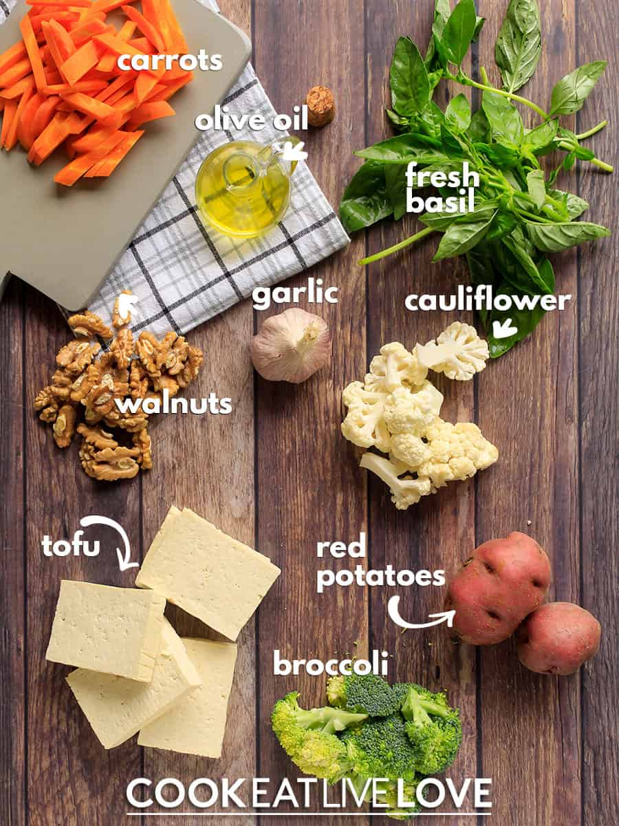 Overhead view of all the ingredients needed to make tofu sheet pan dinner recipe on a wood background with text naming each ingredient.