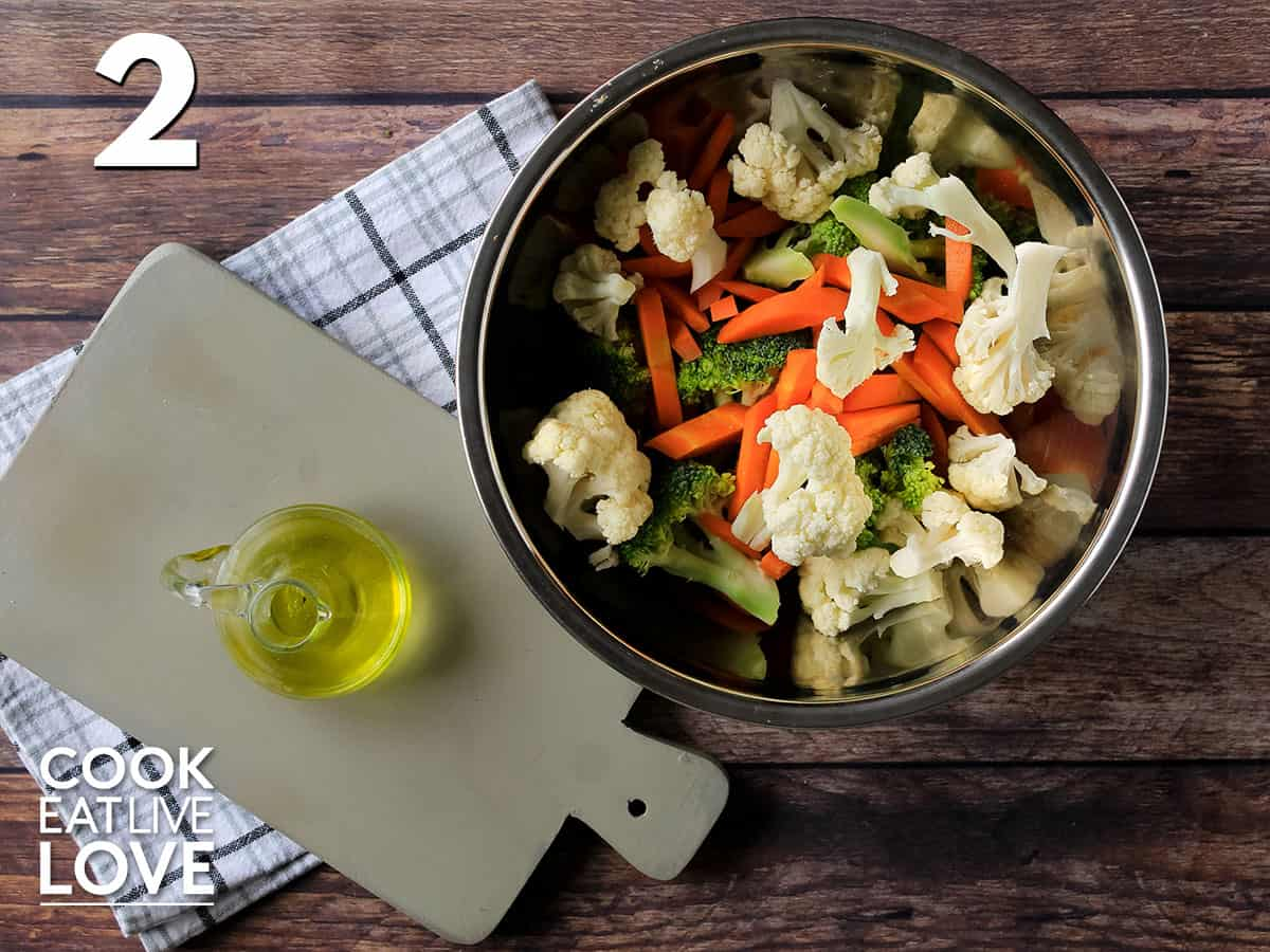 Veggies for the sheet pan dinner are in a bowl ready to toss with olive oil.