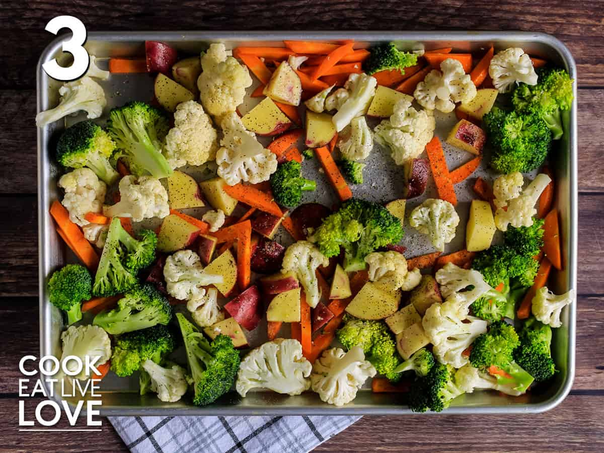 Veggies are spread out on sheet pan and ready to bake in the oven.