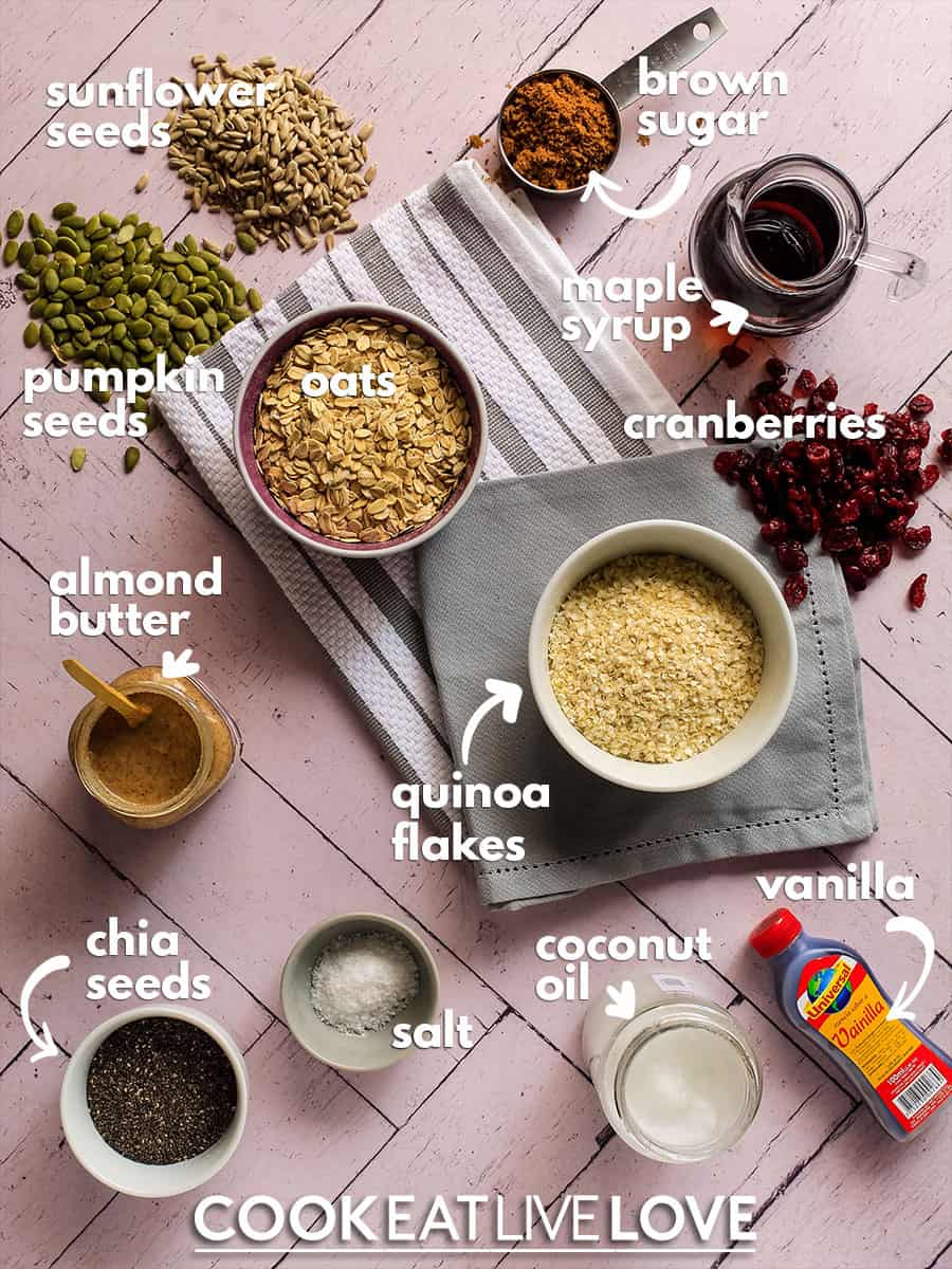 Overhead view of ingredients to make vegan granola bars on pink backdrop with text labels for each.