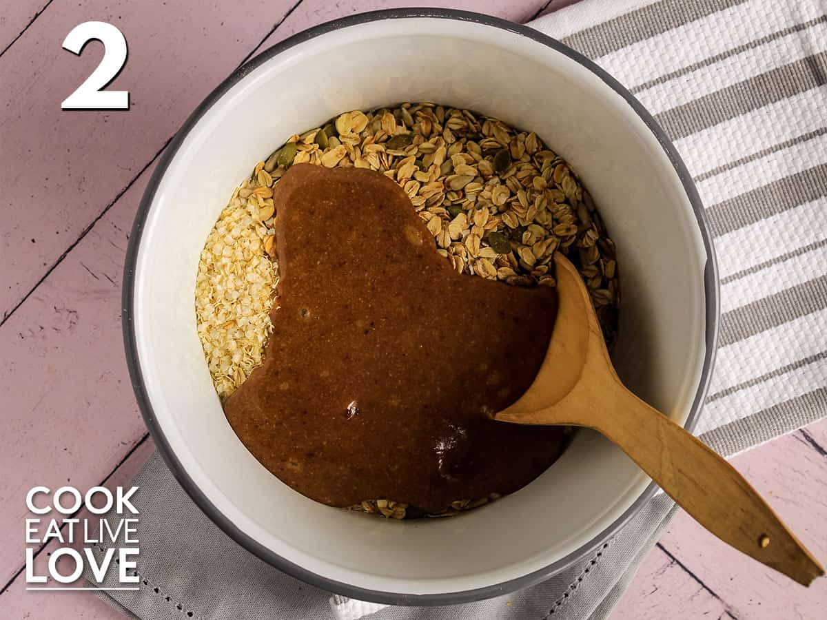 Oats and syrup in a white bowl with wooden spoon.