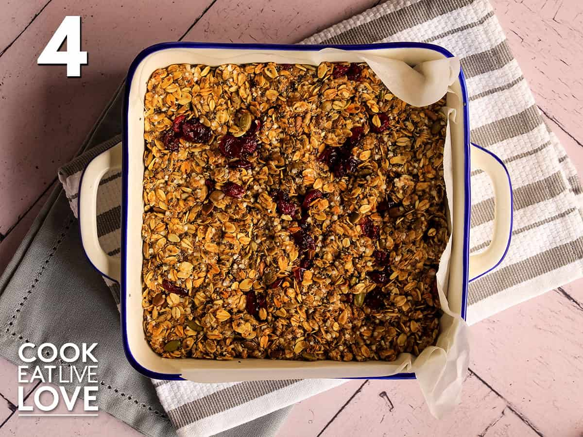 Vegan granola bar mixture is in square pan and pressed firmly down.