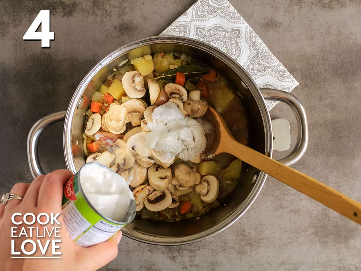 Can of coconut milk is being added to veggies and other ingredients in soup pot.
