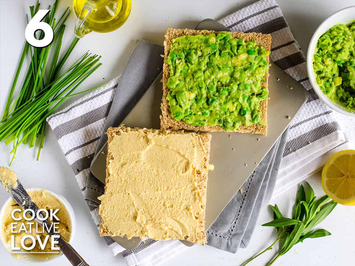Bread on a plate topped with pea avocado spread and hummus
