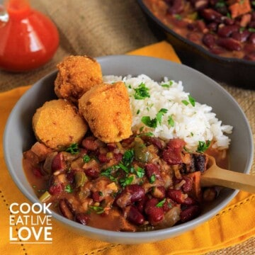 Bowl of red beans and rice with hushpuppies on a table