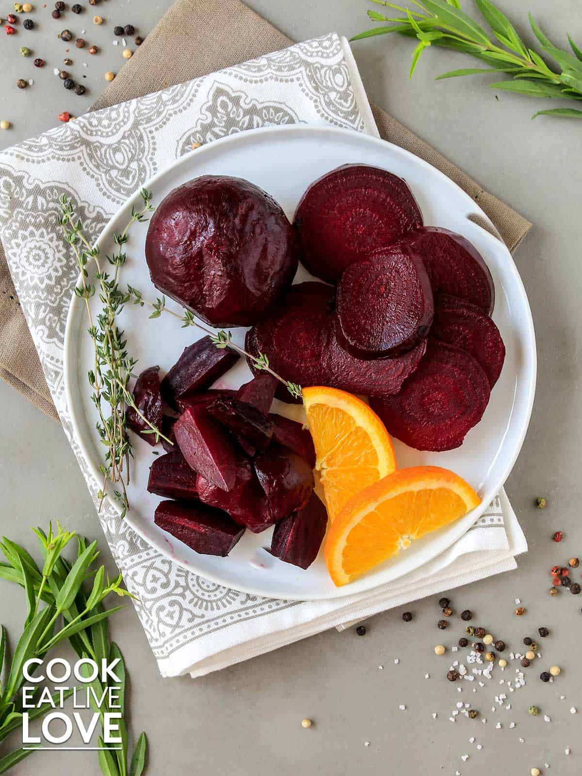Beets on a plate garnished with orange slices and fresh herbs