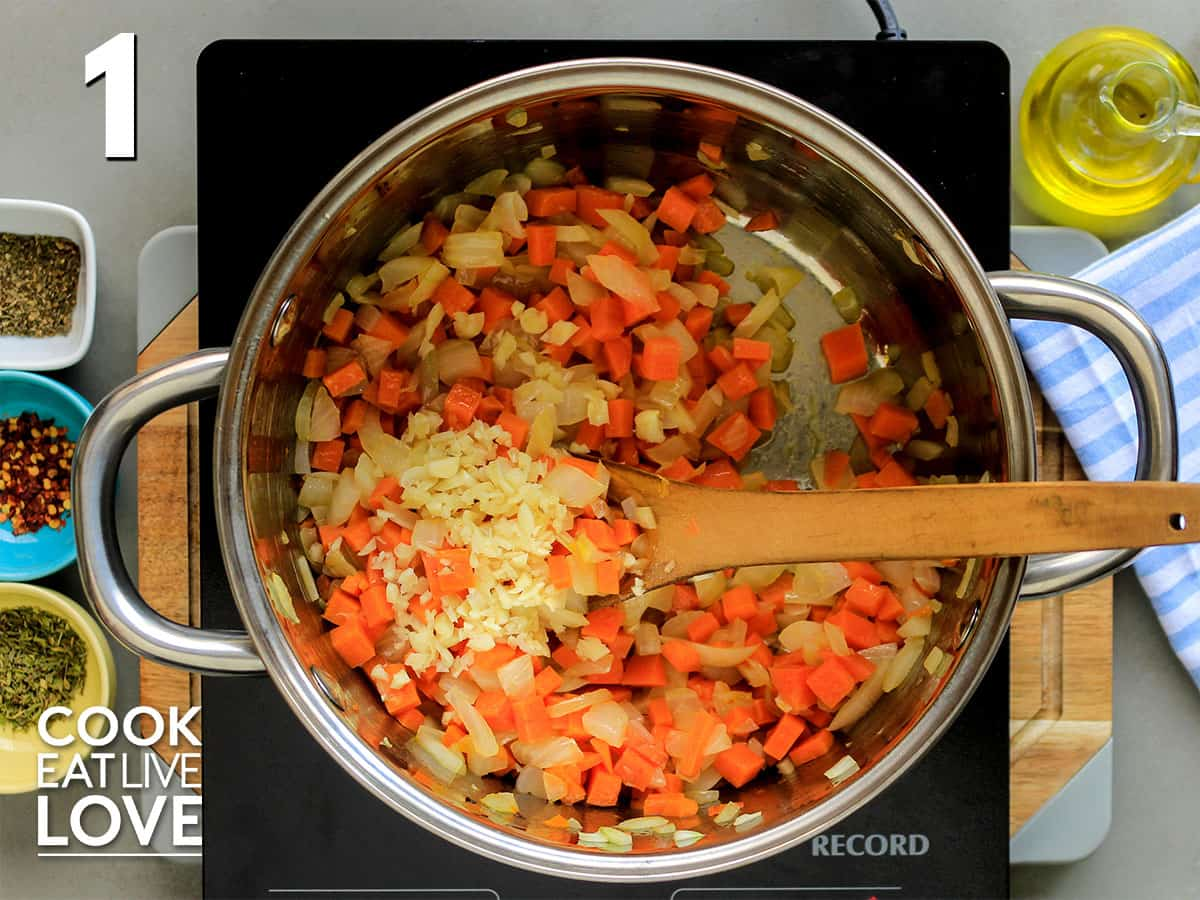 Onions, garlic and carrots in saute pan on burner