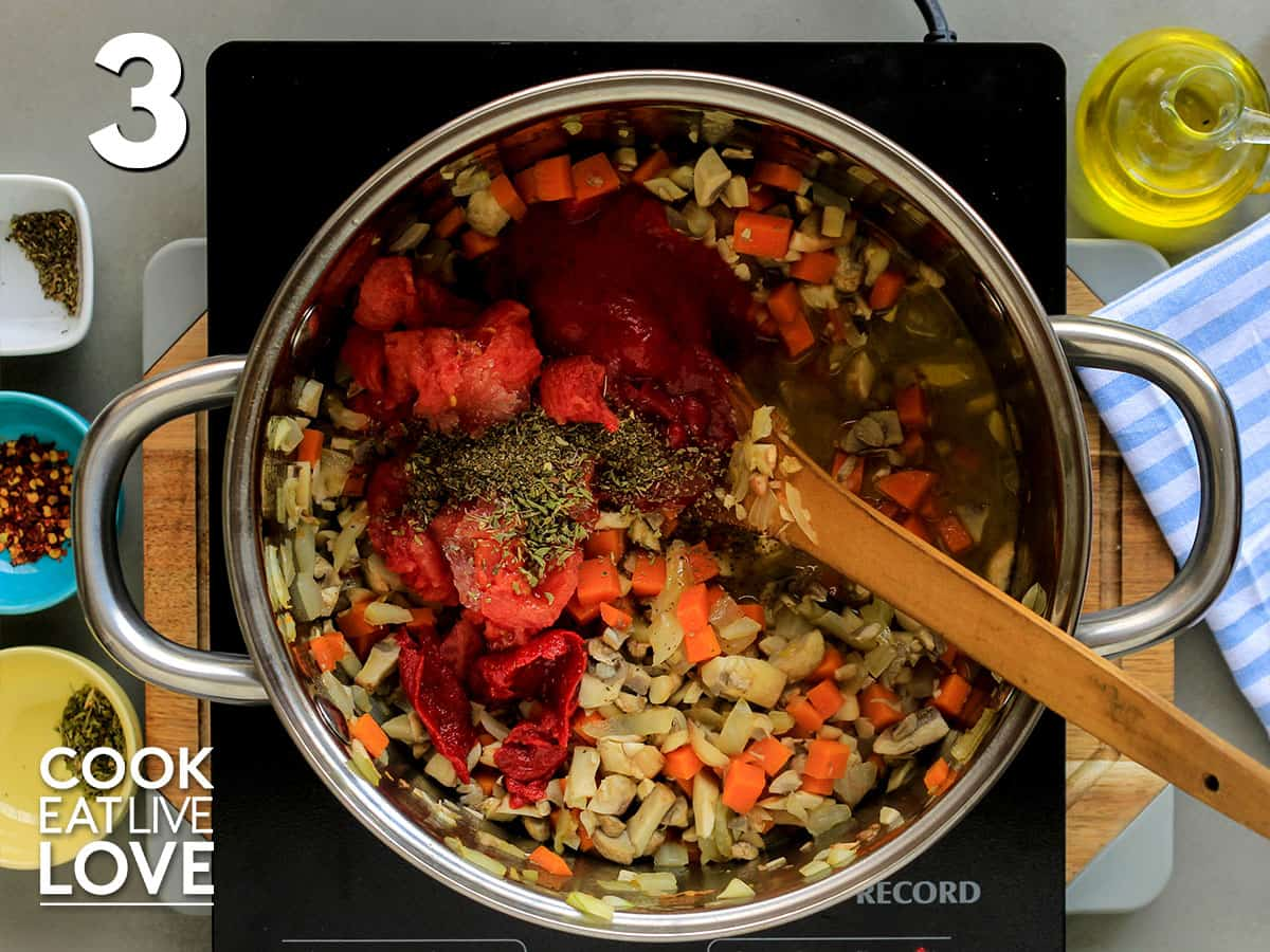 Seasonings and tomatoes added to cooked vegetables in skillet