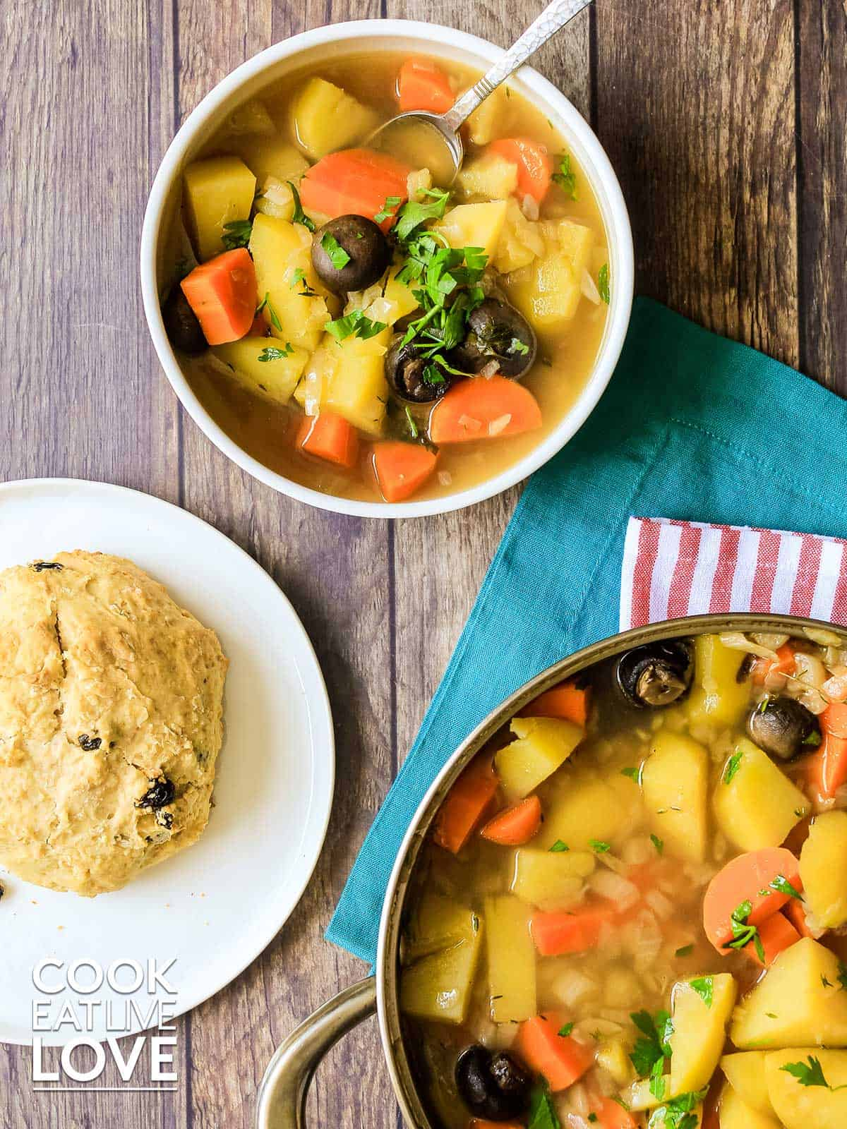 Overhead view of Vegan Irish stew served up in white bowl with soda bread
