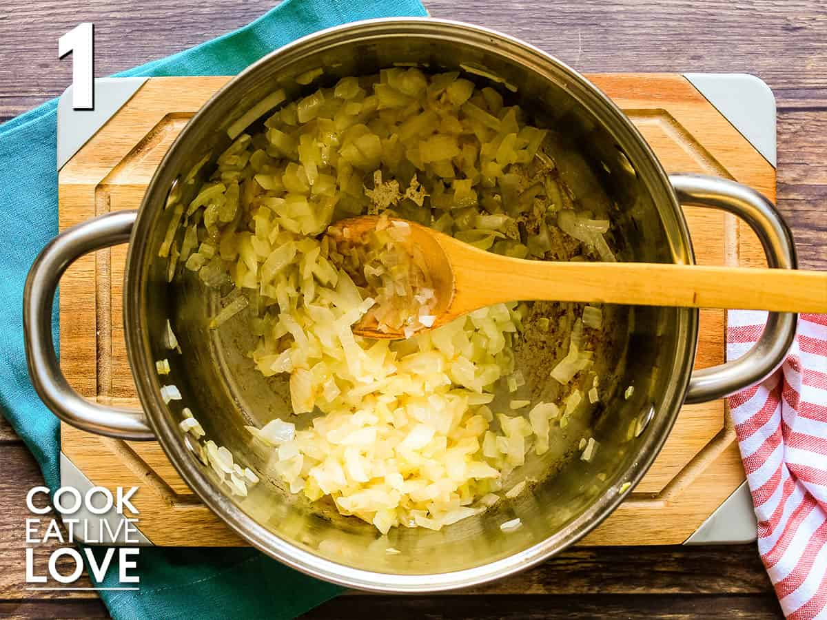 Sauteed onions in a pan with wooden spoon