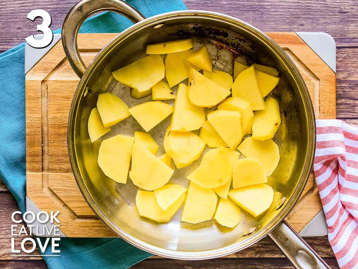 Sliced potatoes layered in pan
