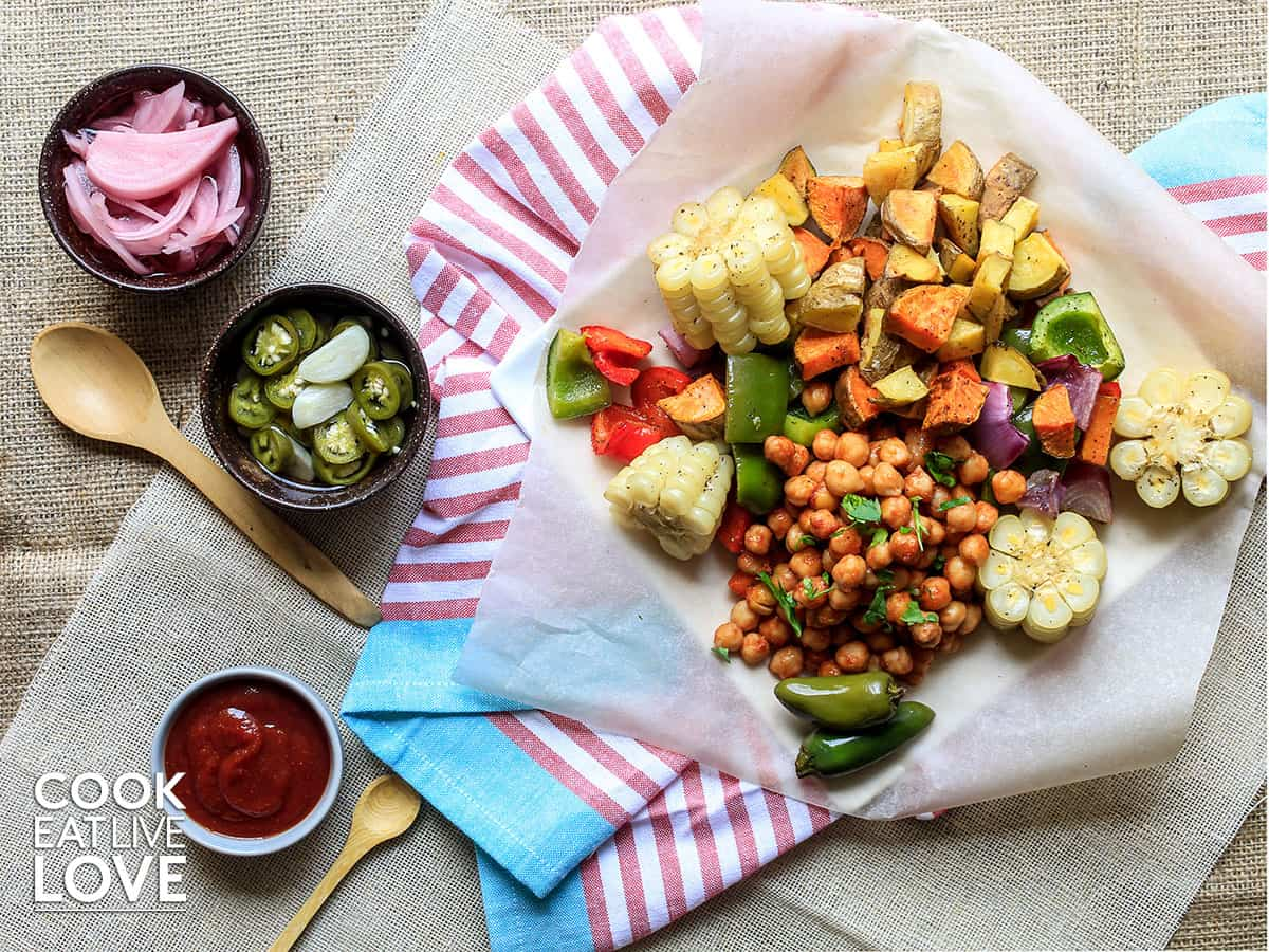 BBQ chickpeas and veggies on baking paper with sauce and jalapenos