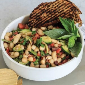 White bowl with cannellini salad garnished with basil and grilled bread