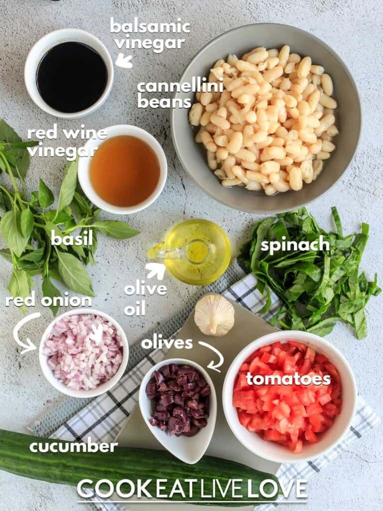 Ingredients to make cannellini bean salad on counter with text labels