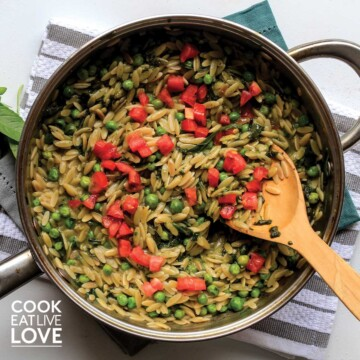 Pesto orzo in a skillet with wooden spoon and topped with tomatoes
