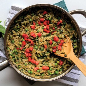 Pesto orzo in pot garnished with diced tomatoes