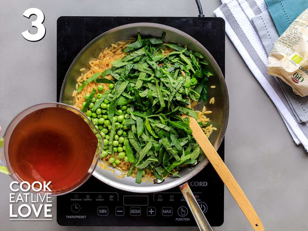 Adding the spinach, peas and broth to the pan of orzo