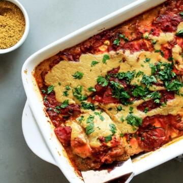 Zucchini lasagna in a casserole dish with spatula.