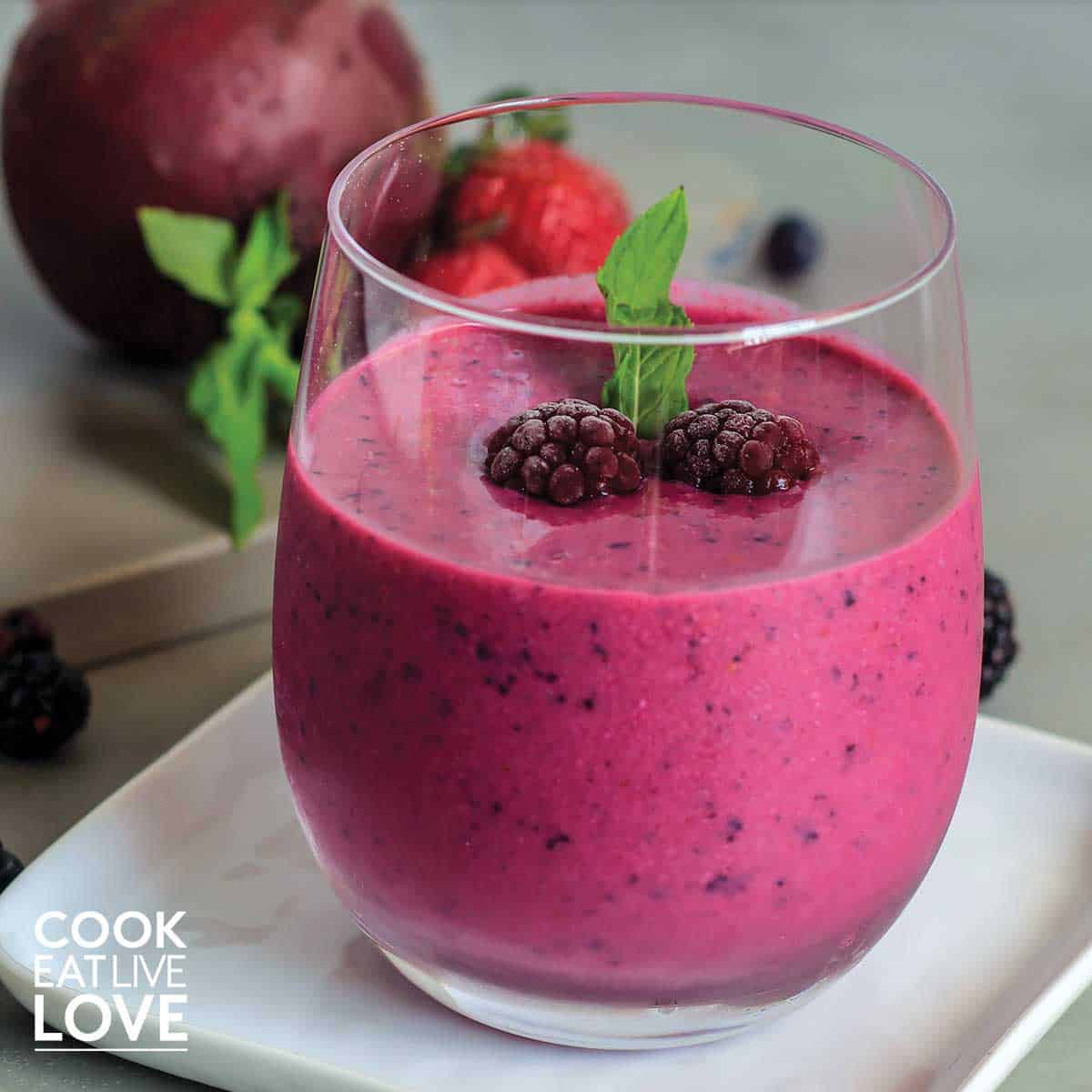 Bright pink smoothie in glass topped with blueberries