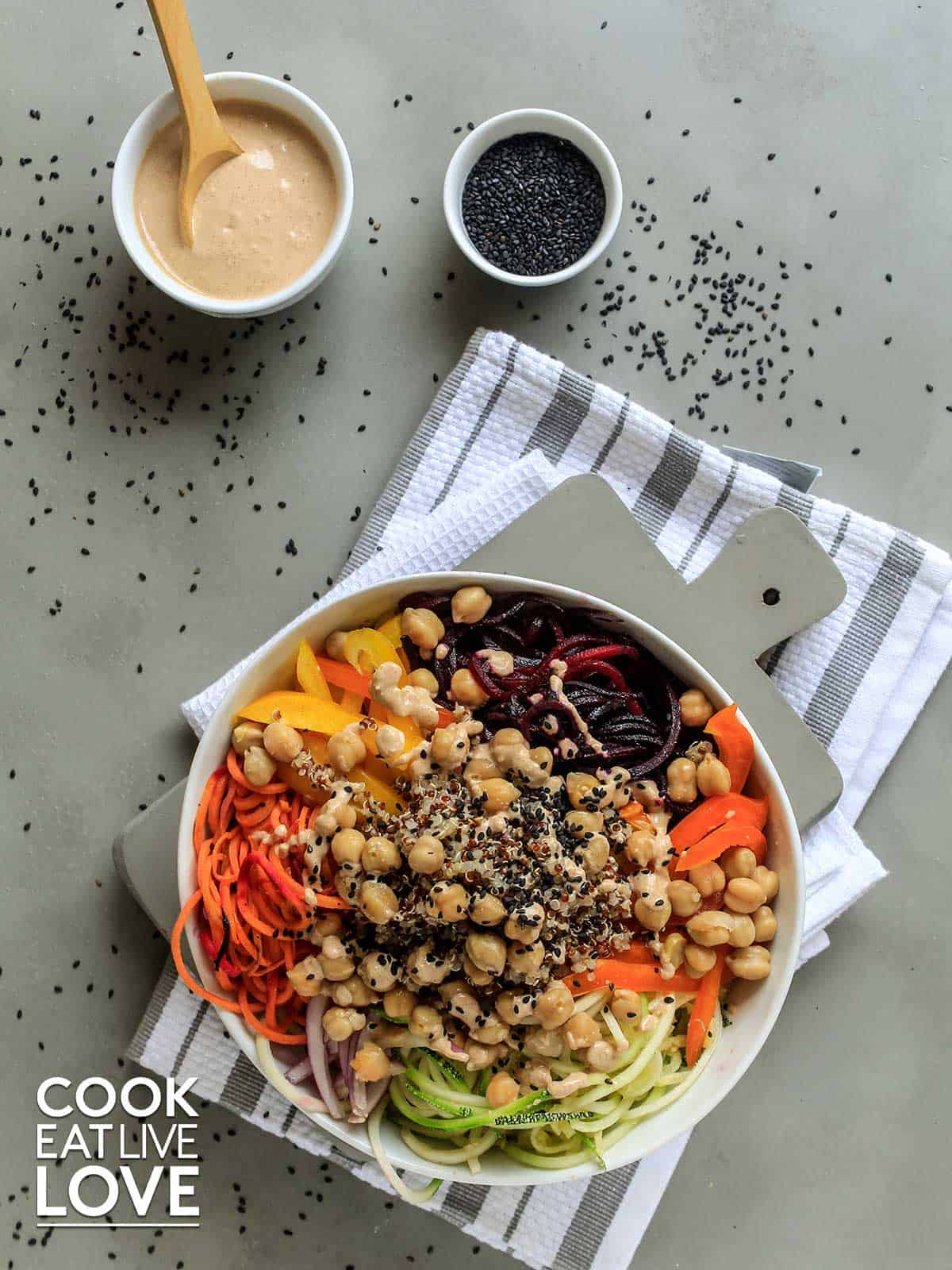 Spiralized veggies in a white bowl with dressing and sesame seeds on the side