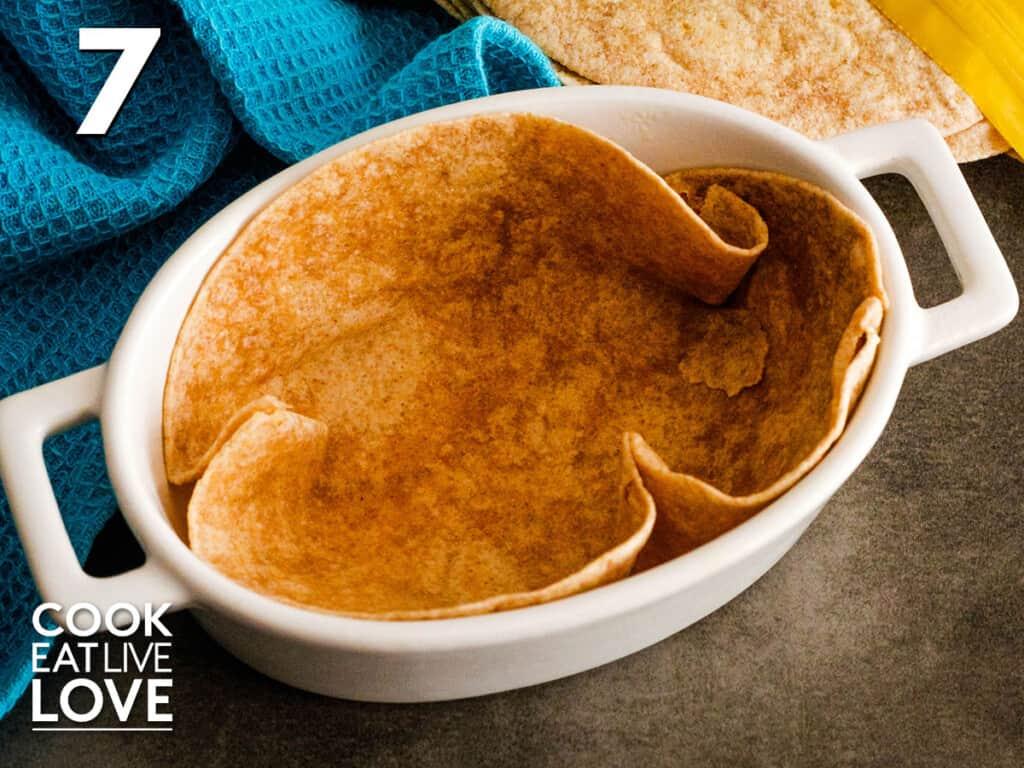 Tortilla shaped into baking dish to make tortilla bowl