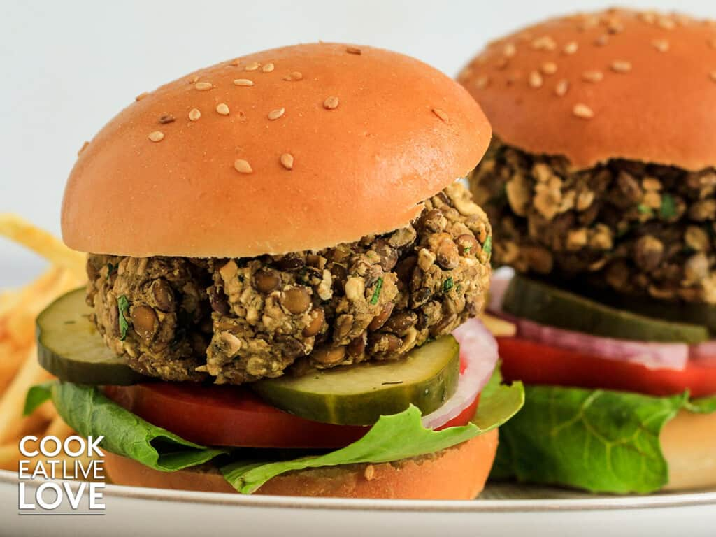 Two lentil sliders on a plate with all the toppings.