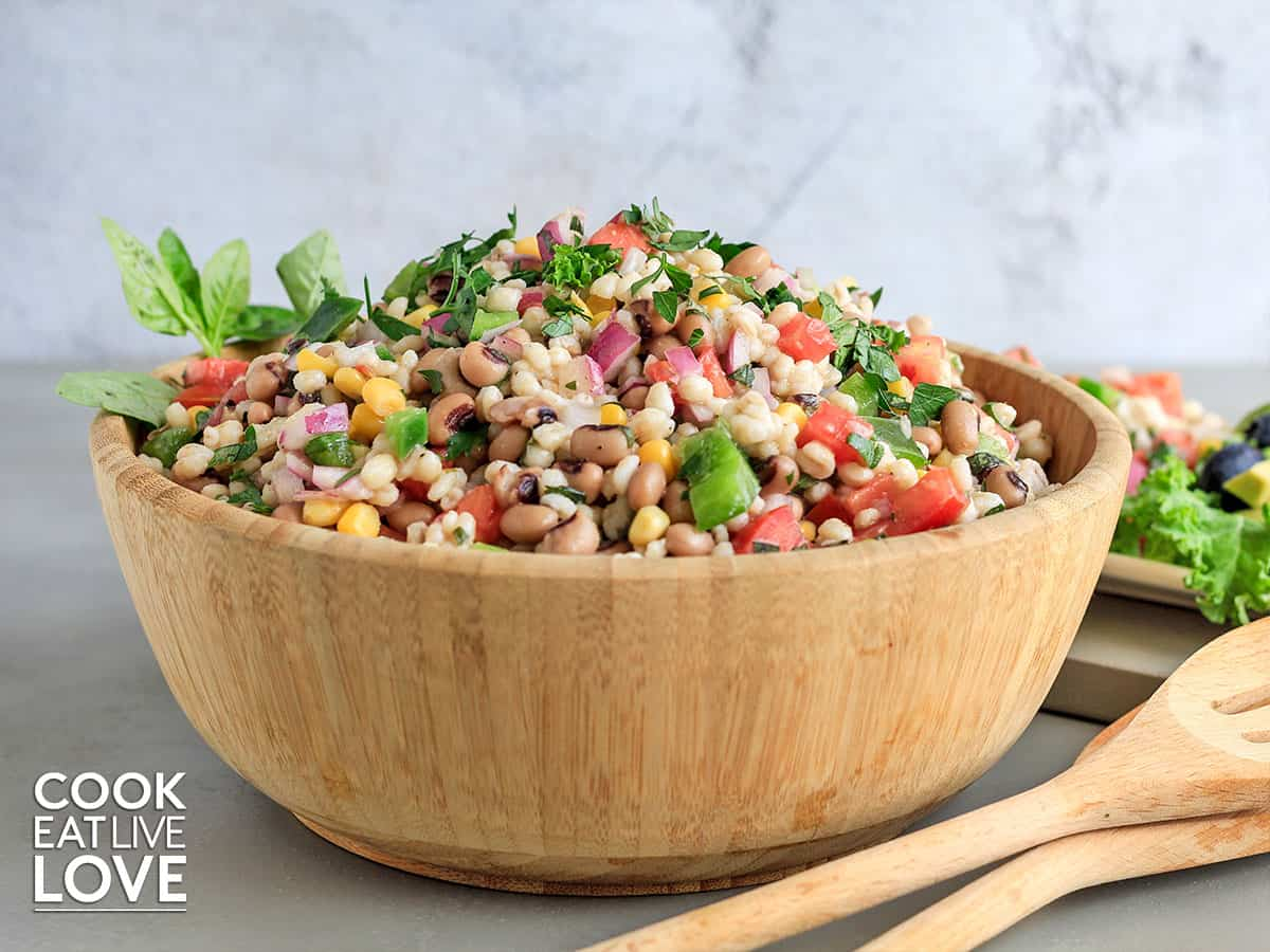 Barley salad served up in wooden bowl with wooden utensils