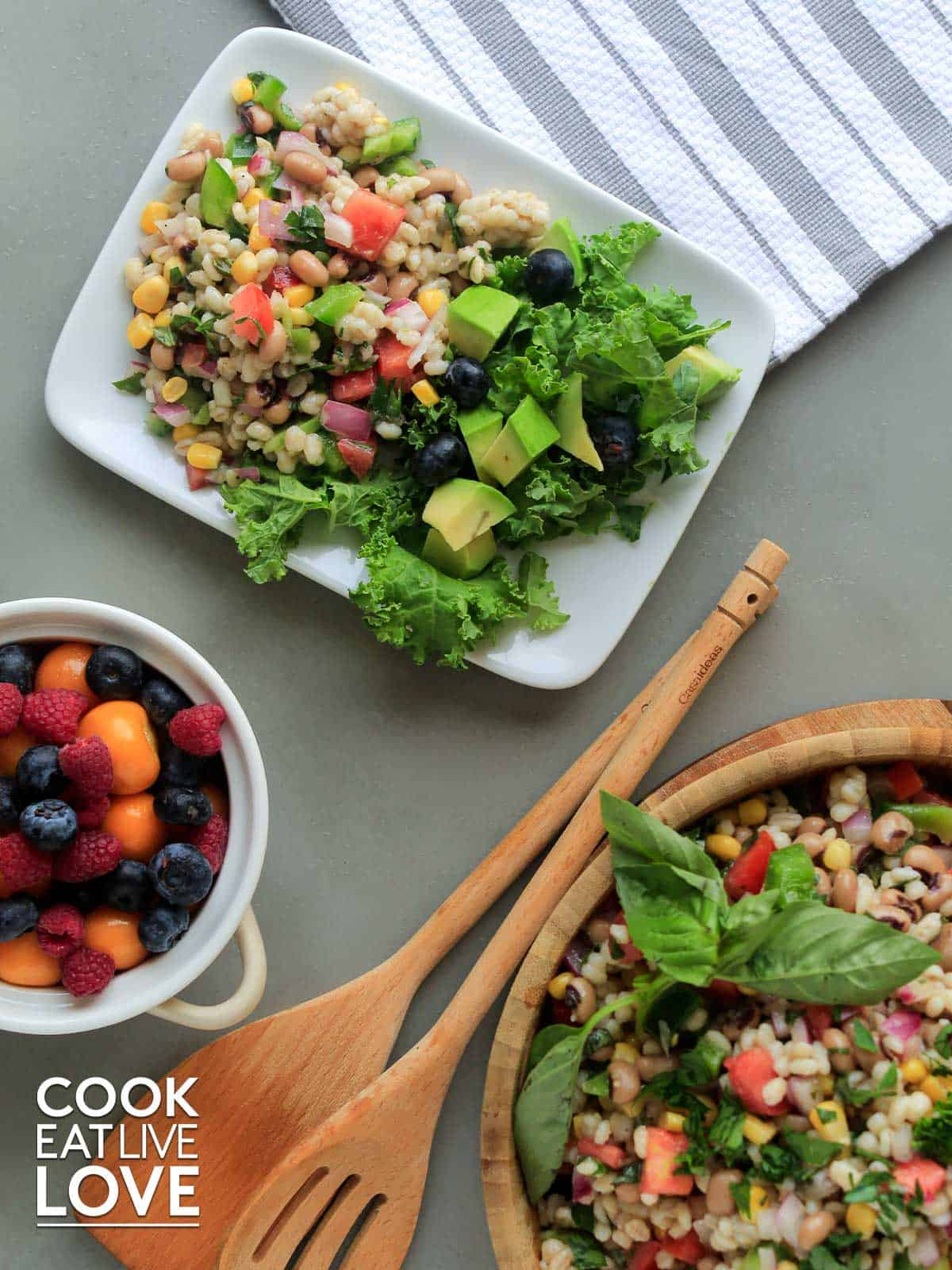 Barley salad served up on a plate with a bowl of salad to the side