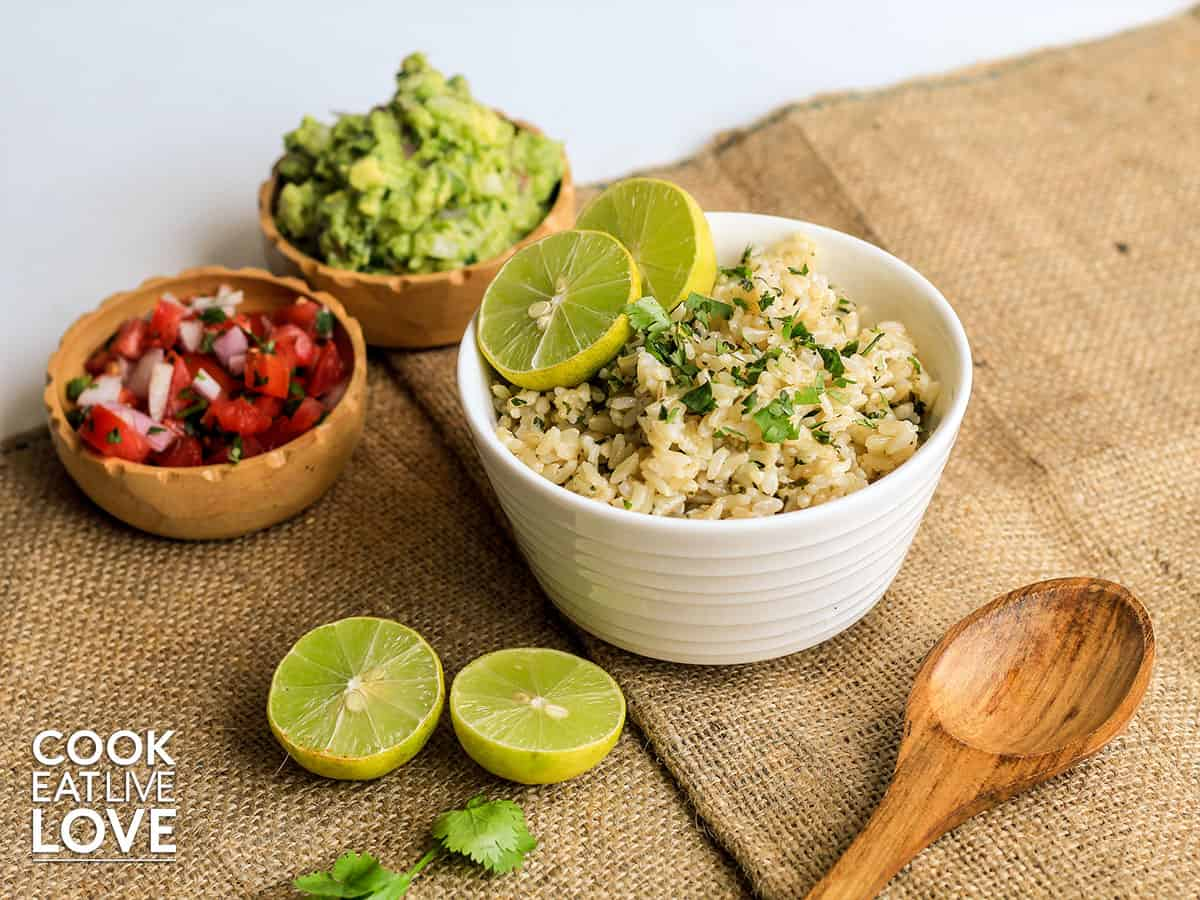 Bowl of instant pot cilantro lime rice with pico de gallo and guacamole on the table